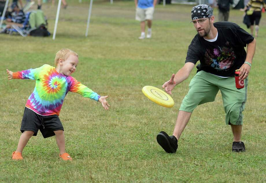 Three-year-old Cyllus Kane, of Uncasville, plays frisbee with his dad Brian on the lawn in front of the main stage at the annual Gathering of the Vibes music festival Saturday, Aug. 2, 2014, at Seaside Park in Bridgeport, Conn. Photo: Autumn Driscoll / Connecticut Post freelance