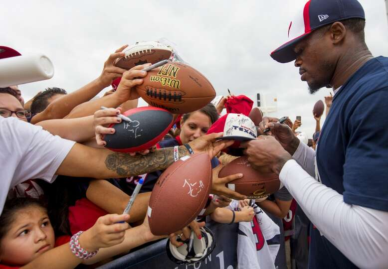 Texans wide receiver Andre Johnson, right, signs autographs.