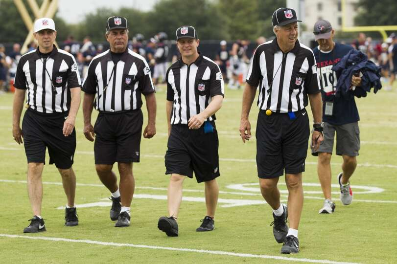 NFL officials, visiting Texans training camp, walk off the field at the end of practice.