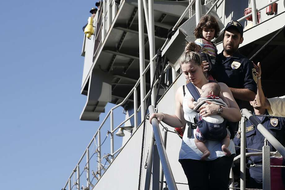 A woman evacuated from Libya carries her baby upon arrival at Piraeus, a port near Athens. Photo: Petros Giannakouris, Associated Press