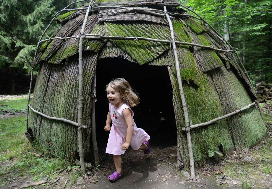 Molly Gorra, 4, of Baltimore, runs out of a replica Algonkian wigwam at the 10th annual Green Corn Festival at the Institute for American Indian Studies in Washington, Conn. Saturday, Aug. 2, 2014.  The festival welcomed the first corn of the season and celebrated American Indian heritage and culture with music, dance, demonstrations, crafts, storytelling and food. Photo: Tyler Sizemore / The News-Times
