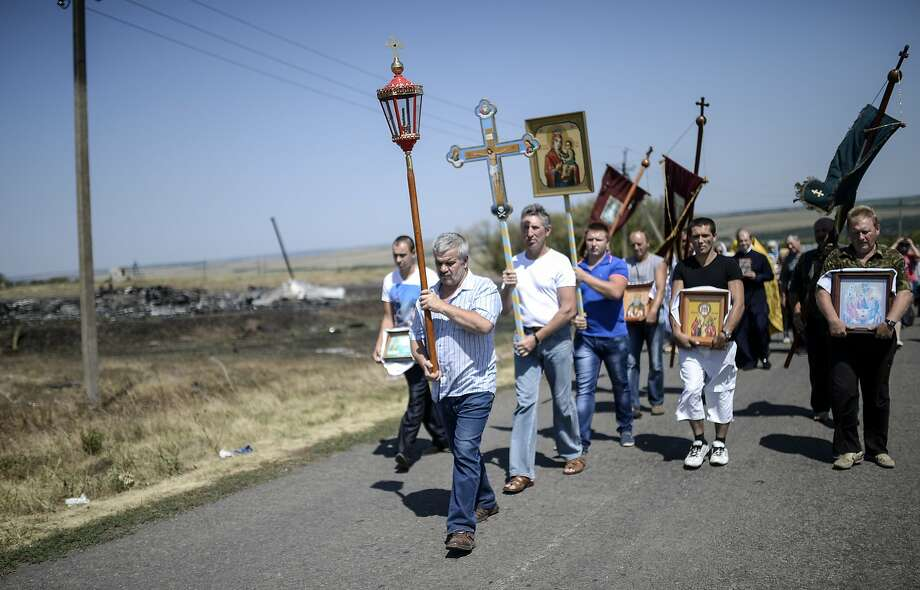 People attend a religious ceremony outside the crash site of Malaysia Airlines Flight 17 near  the village of Hrabove, about 50 miles east of Donetsk, Ukraine. The crash killed 298 people. Photo: Bulent Kilic, AFP/Getty Images