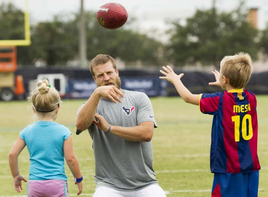 Texans quarterback Ryan Fitzpatrick, left, plays catch with his daughter, Lucy, 3, and son, Tate, 5, after practice. Photo: Brett Coomer, Houston Chronicle
