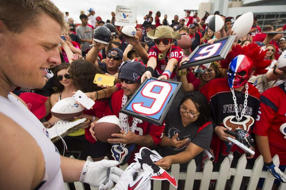 Texans defensive end J.J. Watt, left, signs autographs. Photo: Brett Coomer, Houston Chronicle