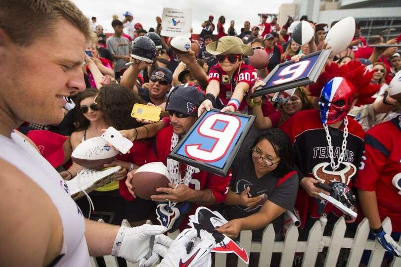 Texans defensive end J.J. Watt, left, signs autographs.