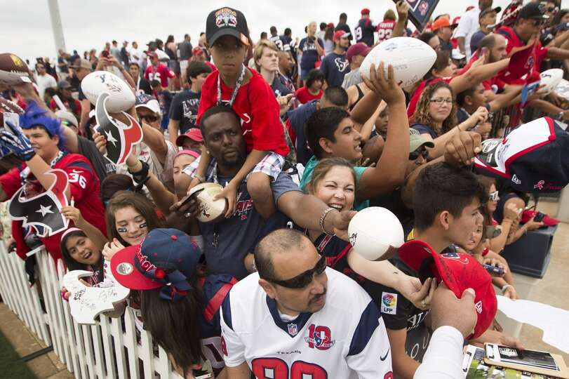 Texans fans reach out for tackle Duane Brown to sign autographs.