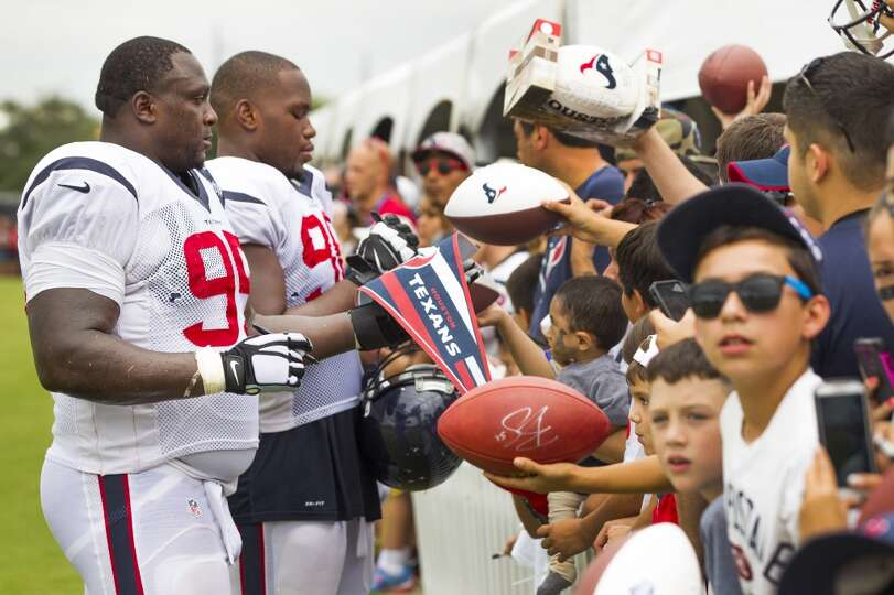 Texans nose tackle Jerrell Powe (95) and defensive end Tim Jamison (96) sign autographs.