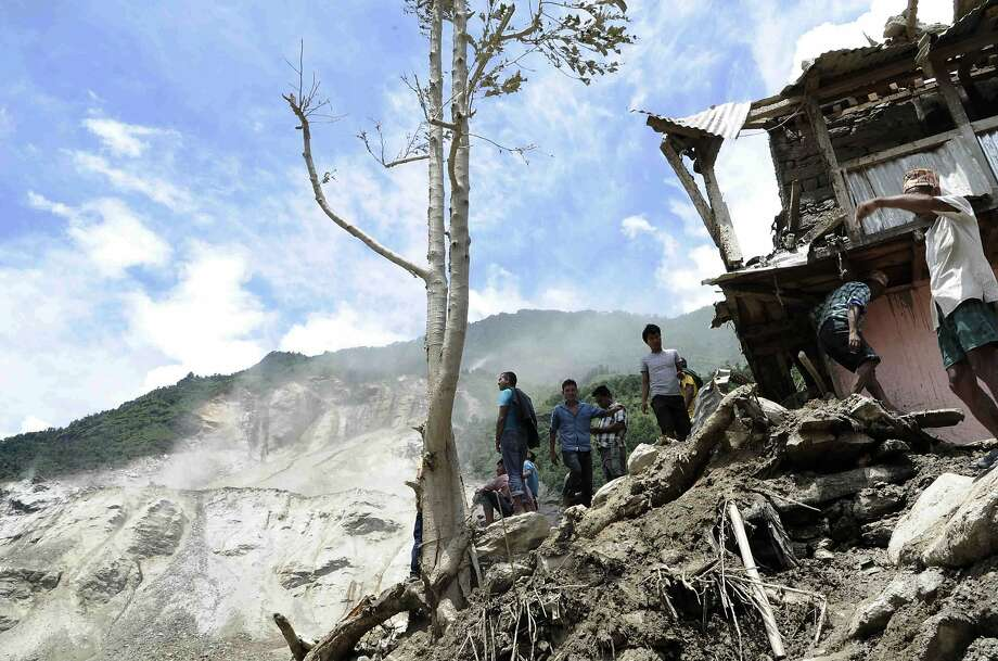 Residents near damaged homes survey a landslide near the Sunkoshi River northeast of Kathmandu. Eight bodies were found, and scores are missing. Photo: Nepal Army, AFP/Getty Images