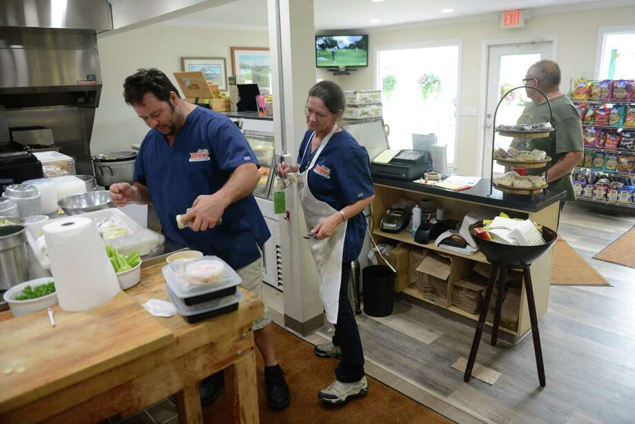 Owner Stephen Merkel and employee Roberta work in the kitchen at Steve's Deli in New Milford, Conn. Friday, Aug. 1, 2014.  Steve's Deli recently opened beside Valley Golf Center and the two businesses feed off each other's customers to improve business. Photo: Tyler Sizemore / The News-Times