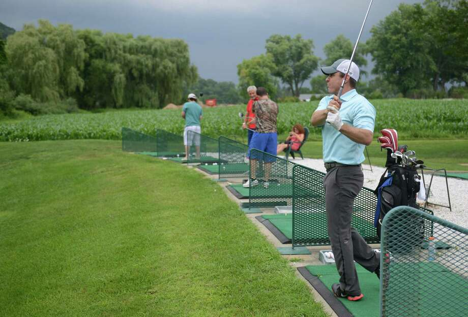 Chris Velander, of New Milford, hits from the driving range at Valley Golf Center in New Milford, Conn. Friday, Aug. 1, 2014.  Steve's Deli recently opened beside Valley Golf Center and the two businesses feed off each other's customers to improve business. Photo: Tyler Sizemore / The News-Times