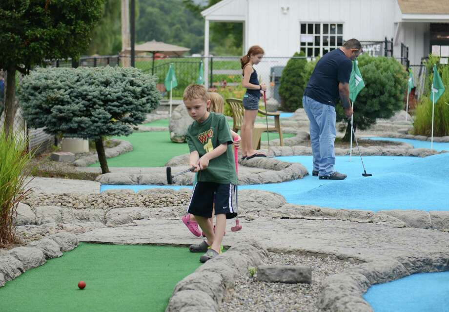 Miles Frosch, 5, of Brookfield, hits a putt at the mini golf course of Valley Golf Center in New Milford, Conn. Friday, Aug. 1, 2014.  Steve's Deli recently opened beside Valley Golf Center and the two businesses feed off each other's customers to improve business. Photo: Tyler Sizemore / The News-Times