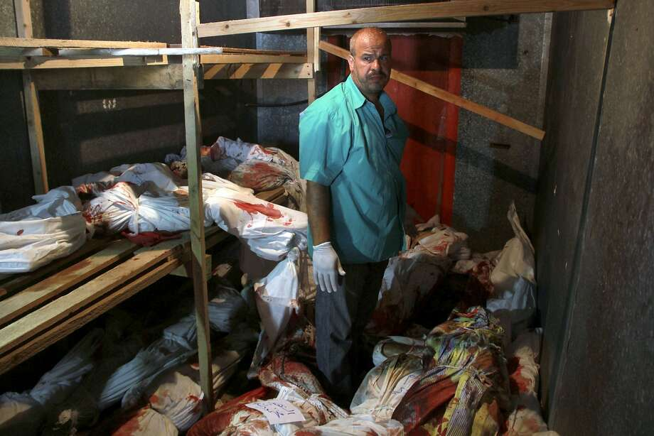 Bodies of Gaza war victims, shown with a medic standing among them, are stored in a food refrigerator in Rafah because the town morgue is full. Photo: Hatem Ali, Associated Press