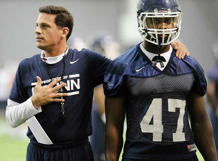 Connecticut head coach Bob Diaco, left stands by player Reuben Frank, right, while talking to his team during the first NCAA college football practice, Saturday, Aug. 2, 2014, in Storrs, Conn. (AP Photo/Jessica Hill) Photo: Jessica Hill, Associated Press / Associated Press