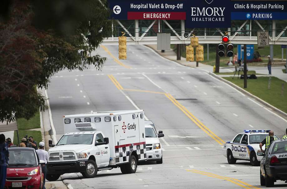 An ambulance transporting a doctor infected with Ebola is escorted by police to a hospital in Atlanta. Photo: David Goldman, Associated Press