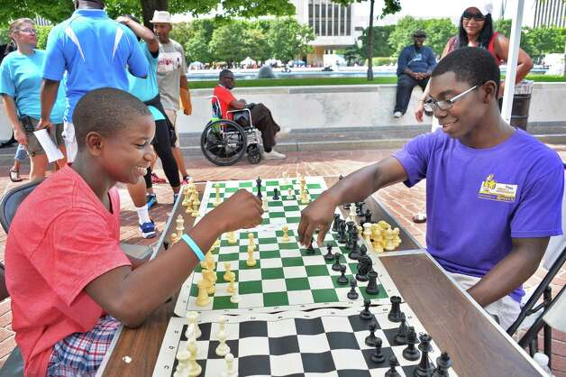 Brothers Zarek Thomas, 14, left, and Ezekiel Thomas,  16, of Waterford play chess at the New York StateOs 2014 African American Family Day at the Empire State Plaza Saturday August 2, 2014, in Albany, NY.  (John Carl D'Annibale / Times Union) Photo: John Carl D'Annibale / 00027122A