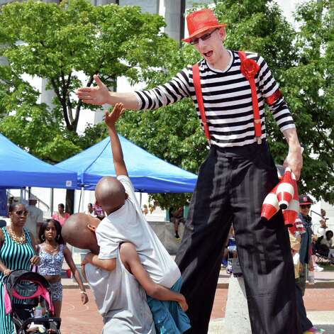 "Uzziah Townsend, 9, left, lifts up Lah'meeer Cooper, 7, both of Albany, to high five street performer Joshua ""Superstar"" Edelman at the New York StateOs 2014 African American Family Day at the Empire State Plaza Saturday August 2, 2014, in Albany, NY.  (John Carl D'Annibale / Times Union) Photo: John Carl D'Annibale / 00027122A"