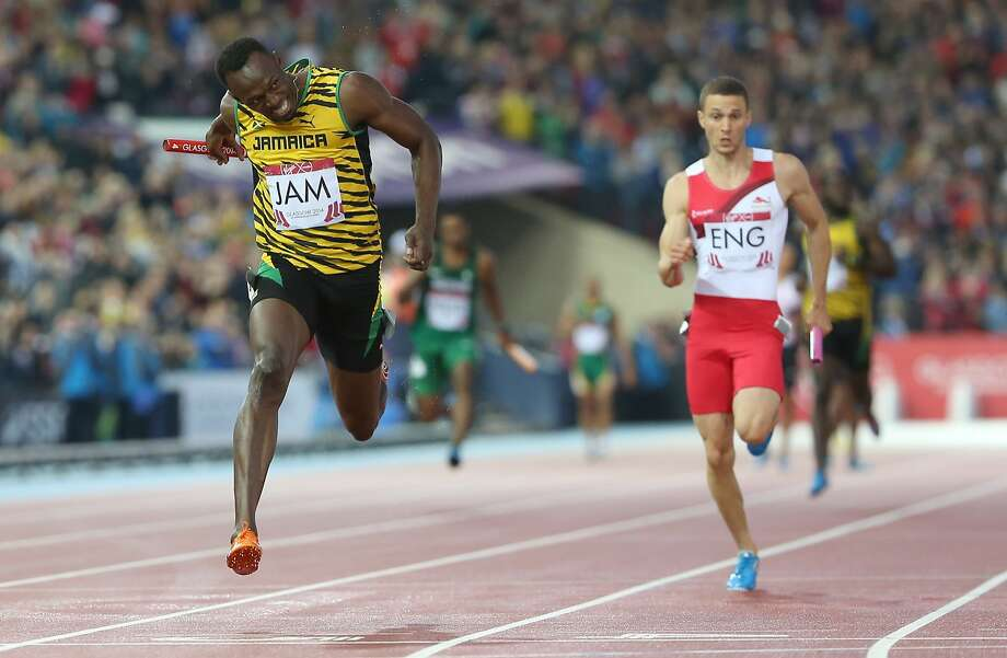 Usain Bolt (left) seals the gold medal for Jamaica as he completes the anchor leg of the men's 4x100 meter relay in Glasgow, Scotland. Photo: Scott Heppell, Associated Press