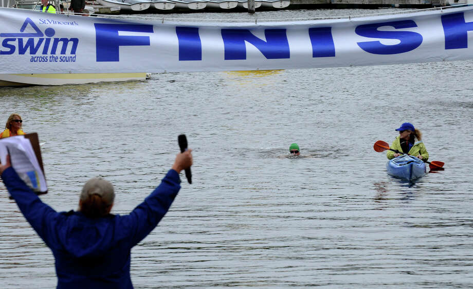 Frank Melbourne, with St. Vincent's Sailfish 1 team, swims across the finish line during St. Vincent's 27th Annual Swim Across the Sound at Captain's Cove in Bridgeport, Conn. on Saturday August 2, 2014. Photo: Christian Abraham / Connecticut Post freelance