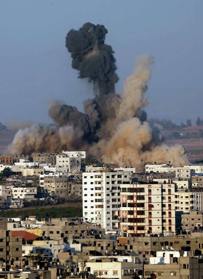 Smoke and sand rise in the air after an Israeli strike, in Gaza City, northern Gaza Strip, Saturday, Aug. 2, 2014. (AP Photo/Hatem Moussa) ORG XMIT: AGAZ103 Photo: Hatem Moussa / AP