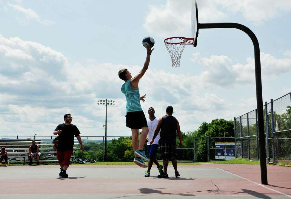 Friends, from left to right, Otis Nadolny, Josh DeSarbo, Jesus Cotto and Edwin Meron play basketball at the courts at Lynch Middle School Wednesday, July 30, 2014, in Amsterdam, N.Y. (Paul Buckowski / Times Union)