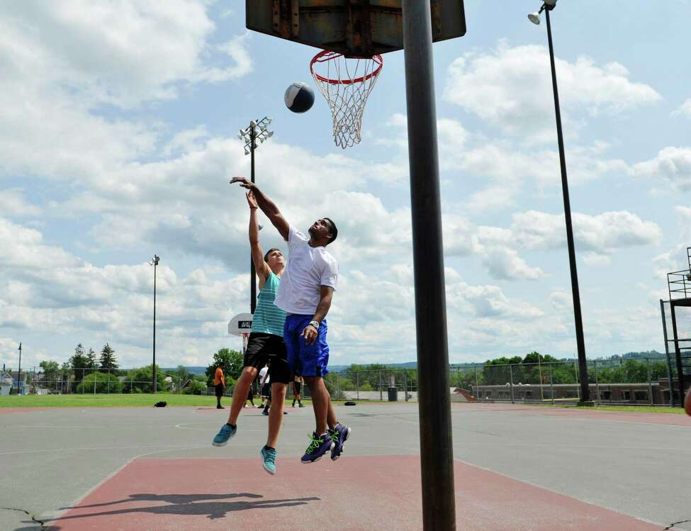 Friends, Josh DeSarbo, left, and Jesus Cotto play basketball at the courts at Lynch Middle School on Wednesday, July 30, 2014, in Amsterdam, N.Y. (Paul Buckowski / Times Union)