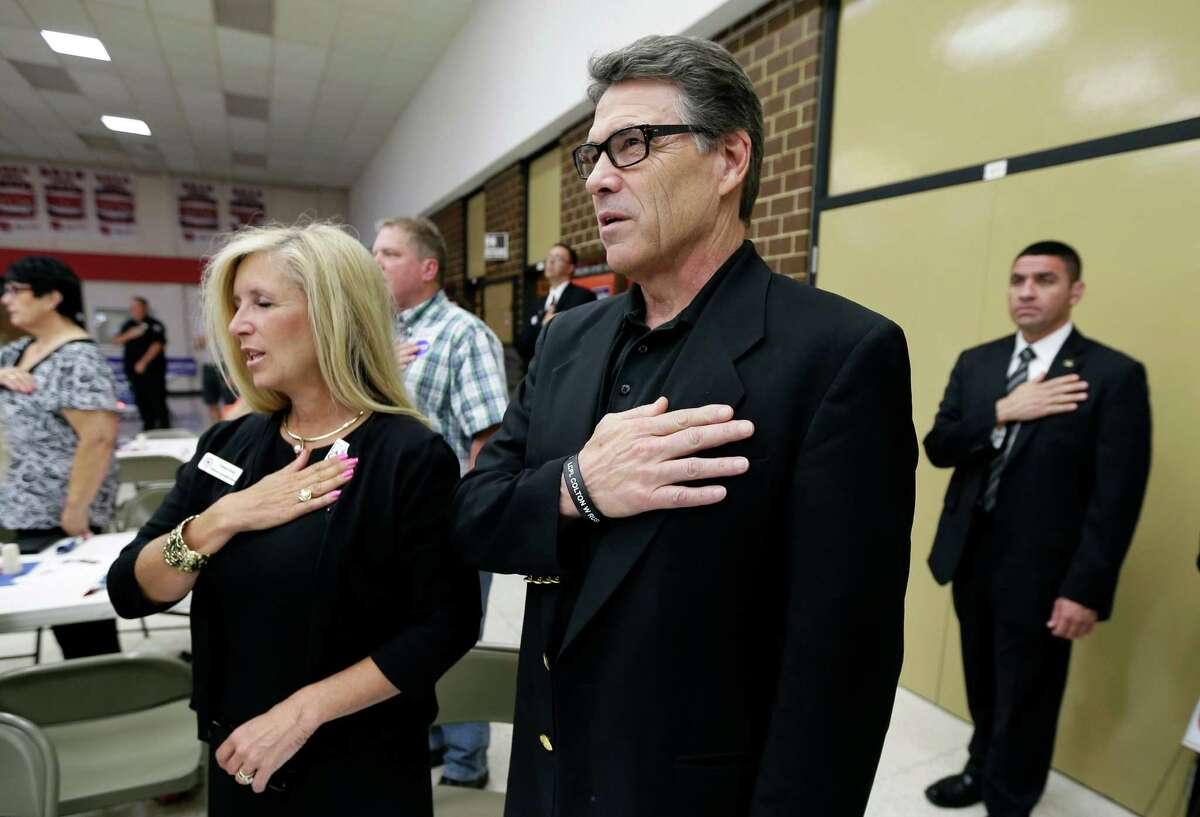 Gov. Rick Perry stands during the national anthem at a meeting with local party activists last month in Algona, Iowa. While Perry's 2012 presidential bid crashed, voters in that primary state may get to decide whether to give him another spin.