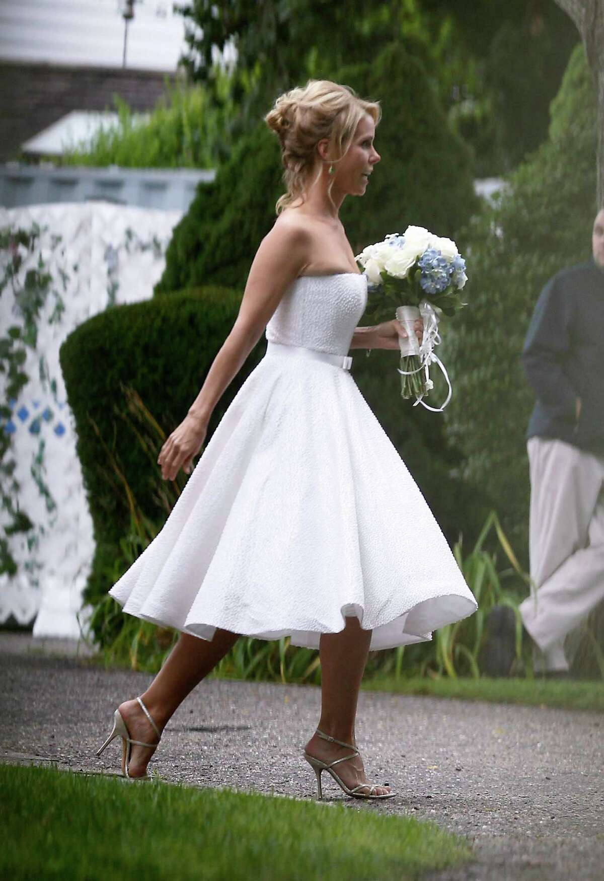 Actress Cheryl Hines walks across a lawn to the tent where her wedding to Robert F. Kennedy Jr., will take place in Hyannis Port, Mass. on Saturday, Aug. 2, 2014. (AP Photo/Stew Milne) ORG XMIT: MASM102