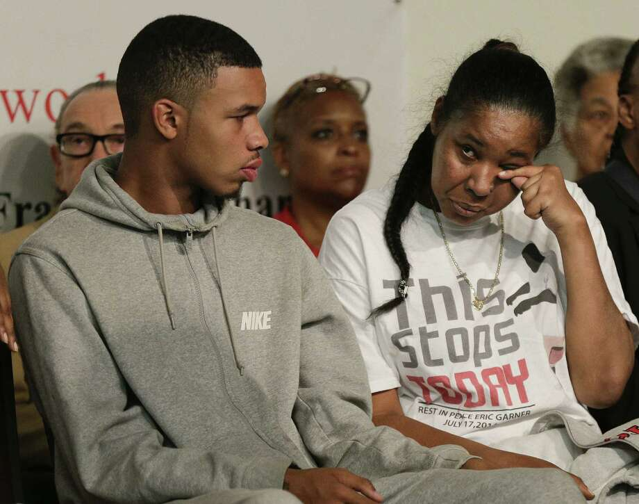 Eric Garner's widow, Esaw Garner, wipes her tears as Garner's son Eric Snipes looks on during a rally held in New York to address the medical examiner's report that came Friday. Photo: Julie Jacobson / Associated Press / AP