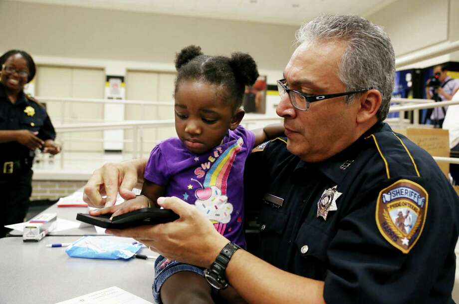 Harris County Sheriff's Deputy Jesse Velasquez fingerprints Tiana Martin, 4, at the Alief Community Health Fair as part of a children's identification project. Tiana was among thousands at back-to-school events on Saturday in Houston. Photo: Gary Coronado, Staff / © 2014 Houston Chronicle