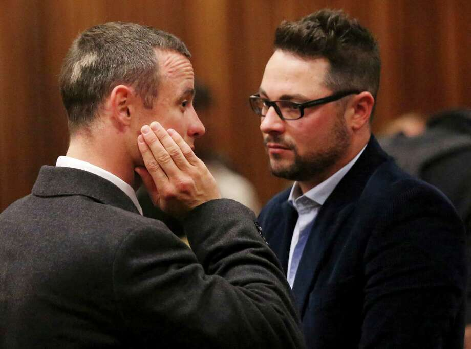 Carl Pistorius, right, was hurt in a car crash. His brother Oscar, left, is on trial accused of murder. Photo: Siphiwe Sibeko, POOL / POOL REUTERS