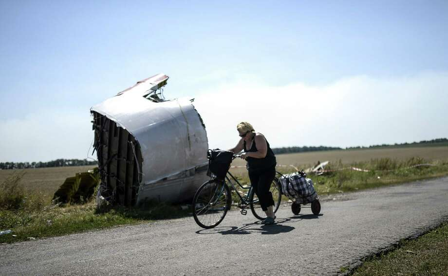 A woman walks with her bicycle near the crash site of the Malaysia Airlines Flight MH17 in the village of Hrabove, some 50 miles east of Donetsk, on Saturday. Photo: BULENT KILIC, Staff / AFP