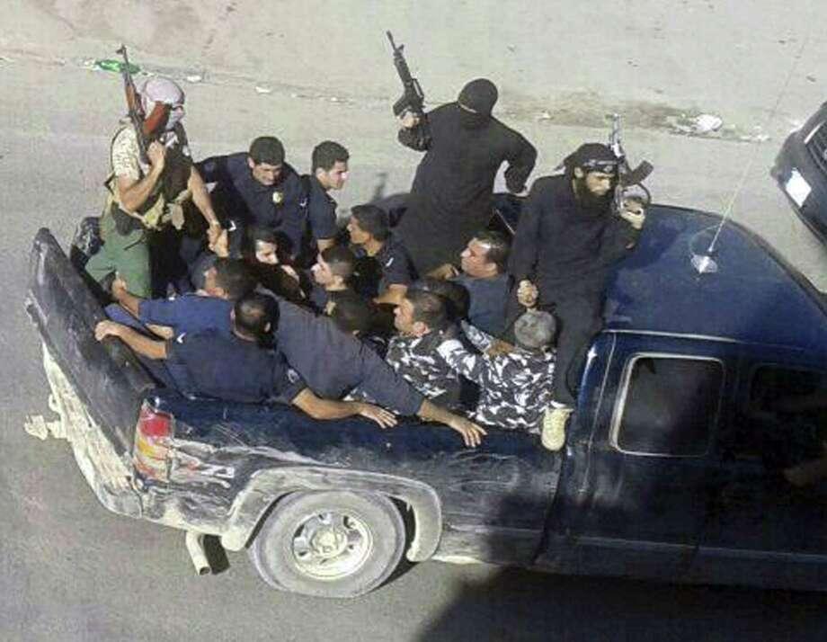 Gunmen drive away with about a dozen men in Arsal, a Sunni Muslim town near the Syrian border in eastern Lebanon. Photo: Associated Press / AP
