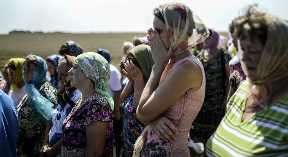 People attend a religious ceremony near the Malaysia Airlines Flight 17 crash site near Hrabove village, about 50 miles east of Donetsk. The jetliner, headed from Amsterdam to Kuala Lumpur, was brought down by a missile on July 17, killing 298 people. Photo: Photos By Bulent Kilic / Getty Images / AFP