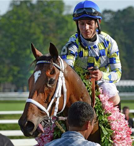 With a garland of Whitney roses Moreno ridden by jockey Junior Alvarado enters the winner's circle after winning the 87th running of The Whitney Saturday afternoon Aug. 2, 2014 at the Saratoga Race Course in Saratoga Springs, N.Y.  (Skip Dickstein/Times Union) ORG XMIT: NYALT Photo: SKIP DICKSTEIN