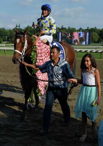 Eleven year old Elle Moreno leads namesake Moreno with jockey Junior Alvarado to the winner's circle after he won the 87th running of The Whitney Saturday afternoon Aug. 2, 2014 at the Saratoga Race Course in Saratoga Springs, N.Y.  (Skip Dickstein/Times Union) ORG XMIT: NYALT Photo: SKIP DICKSTEIN
