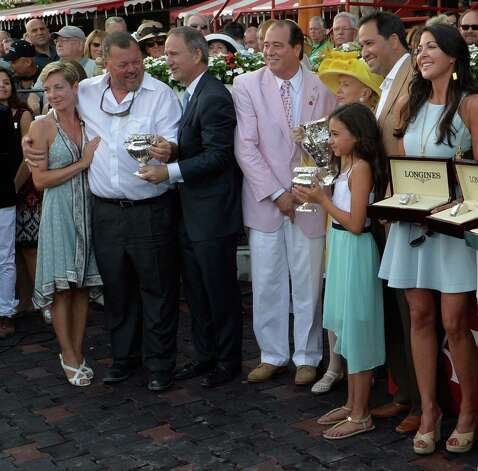 Trainer Eric Guillot, second from left receives the winning trainer's trophy from NYRA CEO Chris Kay, third from left after his charge Moreno won the 87th running of The Whitney Saturday afternoon Aug. 2, 2014 at the Saratoga Race Course in Saratoga Springs, N.Y. With Guillot is Anna Scaible, left;  John Hendrickson, center, Mary Lou Whitney, third from left rear, Michel Moreno, owner, second from left rear, Tiffany Moreno and Elle Moreno, foreground. (Skip Dickstein/Times Union) ORG XMIT: NYALT Photo: SKIP DICKSTEIN