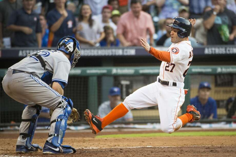 Jose Altuve scores past Blue Jays catcher Josh Thole  during the fifth inning. Photo: Smiley N. Pool, Houston Chronicle
