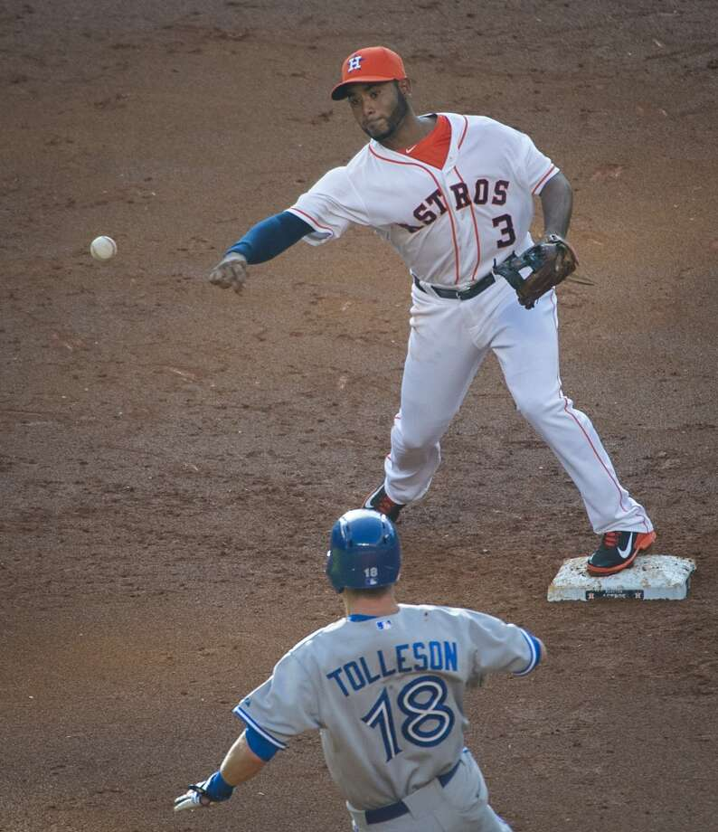 Astros shortstop Gregorio Petit makes the relay to start a double play over Toronto third baseman Steve Tolleson during the second inning. Photo: Smiley N. Pool, Houston Chronicle