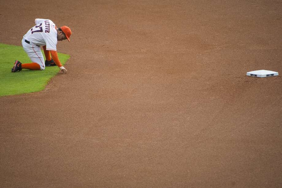 Astros second baseman Jose Altuve writes in the dirt near second base before a game against the Toronto Blue Jays at Minute Maid Park on Saturday, Aug. 2, 2014. Photo: Smiley N. Pool, Houston Chronicle