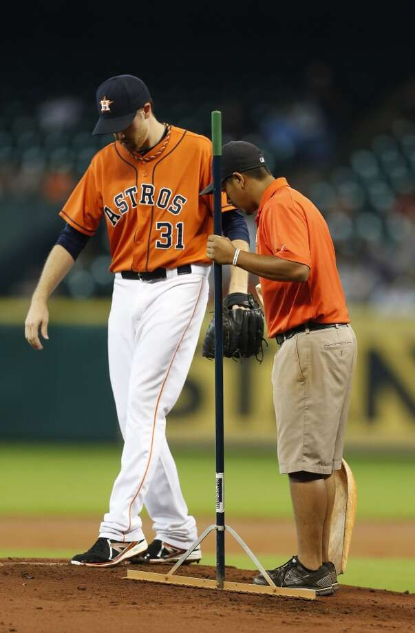 Collin McHugh supervises the grounds crew as they adjust the mound during the first inning. Photo: Karen Warren, Houston Chronicle