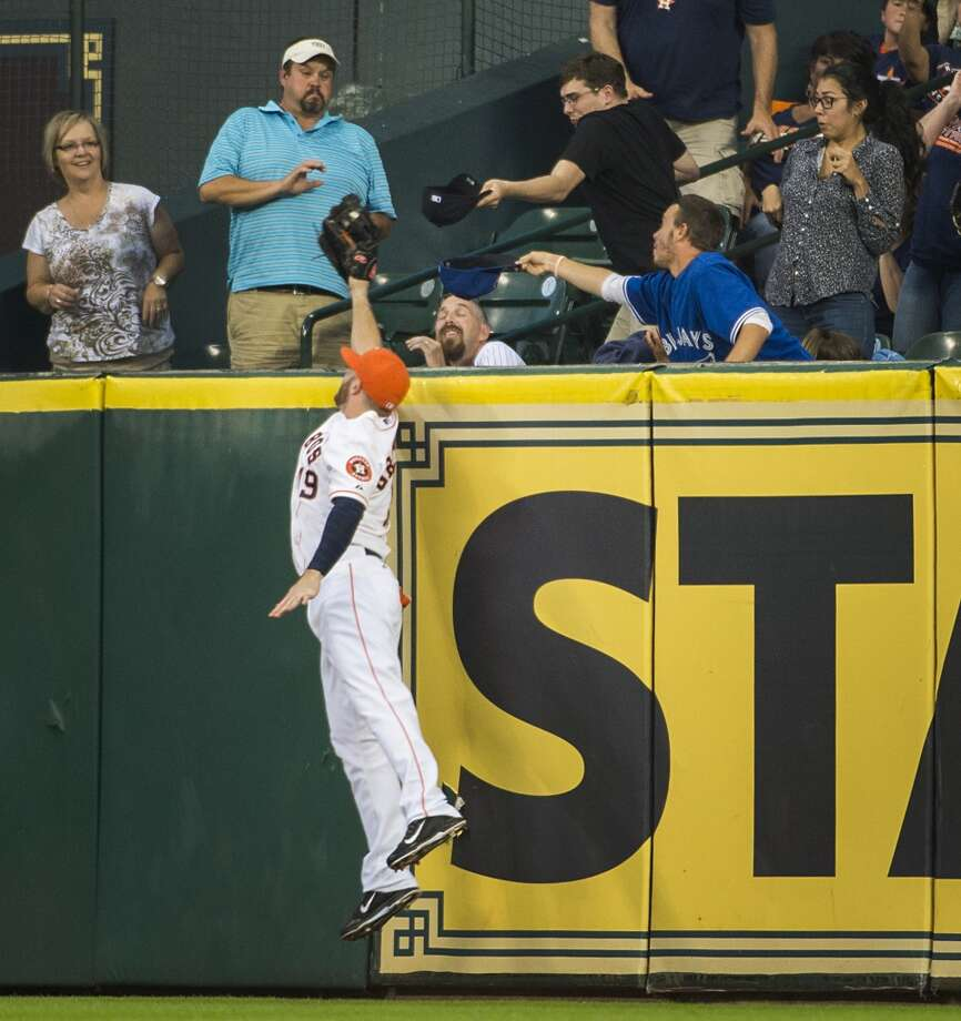 Astros right fielder Robbie Grossman leaps at the wall to rob Toronto pinch hitter Juan Francisco of a home run. Photo: Smiley N. Pool, Houston Chronicle