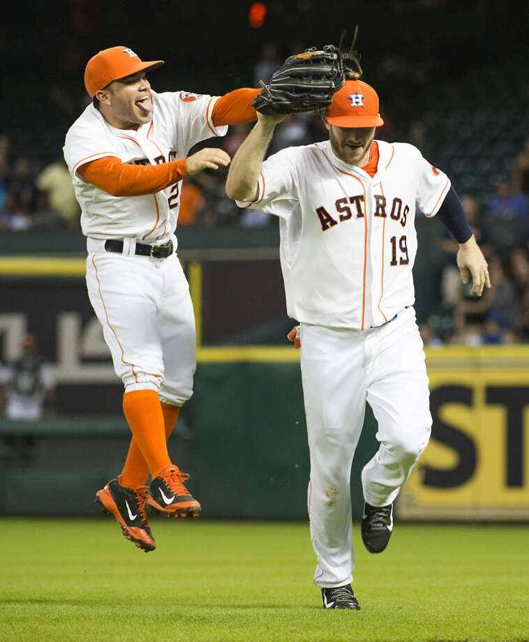 Second baseman Jose Altuve (27) celebrates with right fielder Robbie Grossman after Grossman robbed Toronto  pinch hitter Juan Francisco. Photo: Smiley N. Pool, Houston Chronicle