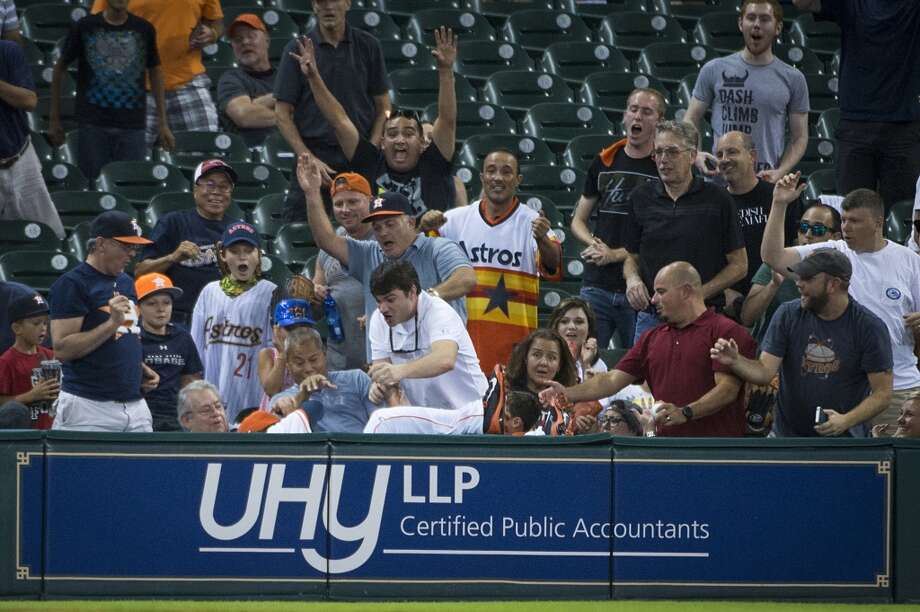 Astros left fielder L.J. Hoes leaps into the stands to catch a foul ball off the bat of Blue Jays pinch hitter Munenori Kawasaki during the ninth inning. Photo: Smiley N. Pool, Houston Chronicle