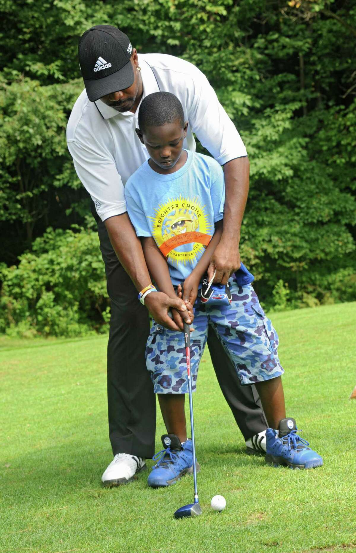 Volunteer Terry Cumberbatch teaches James Stokes, 9, how to hold a golf club as children from the city of Albany get some golf lessons during a program at Colonial Acres Golf Course on Friday, Aug. 1, 2014 in Glenmont, N.Y. (Lori Van Buren / Times Union)