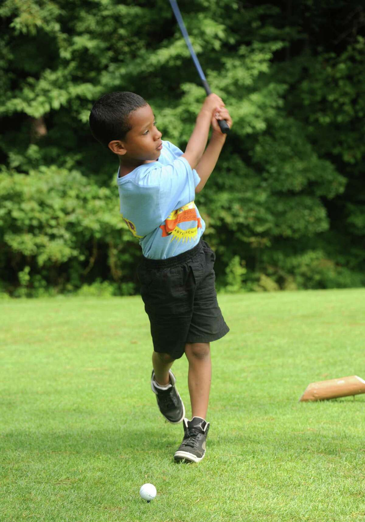 Lorne Johnson, 7, has a nice follow through as he misses his first try on a tee as children from the city of Albany get some golf lessons during a program at Colonial Acres Golf Course on Friday, Aug. 1, 2014 in Glenmont, N.Y. (Lori Van Buren / Times Union)
