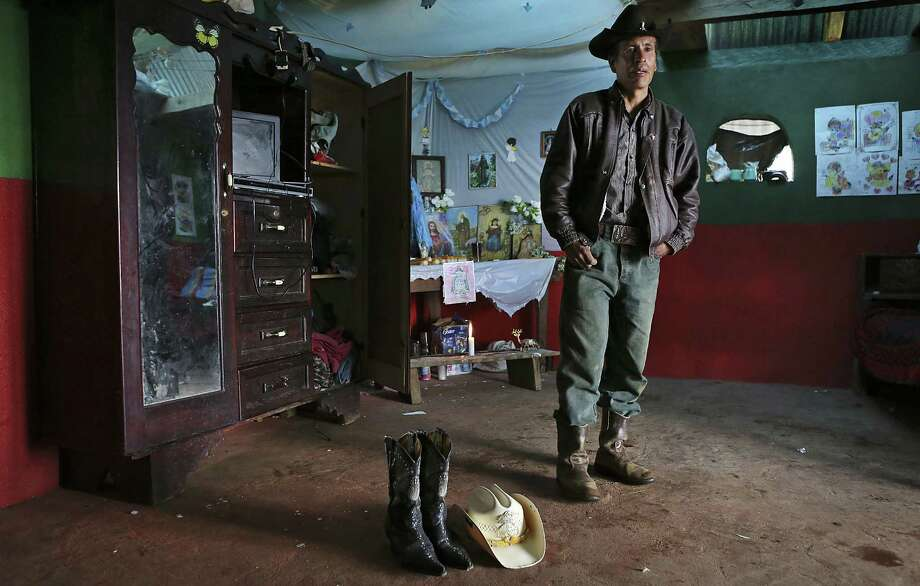 Francisco Ramos Diaz is the father of Gilberto Francisco Ramos Juarez, a 15-year-old whose body was found along the Rio Grande. He displays his son's boots and hat in the living area of their home in San José Las Flores, Guatemala. Photo: Photos By Bob Owen / San Antonio Express-News / ©2013 San Antonio Express-News