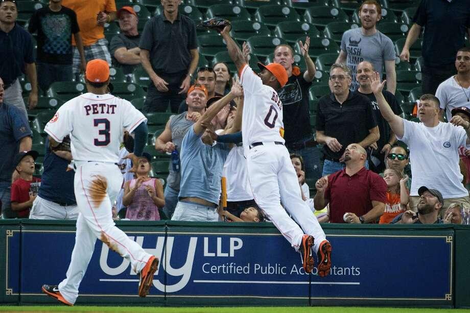 Astros left fielder L.J. Hoes leaps to catch a foul pop-up off the bat of Toronto pinch hitter Munenori Kawasaki before falling into the stands in the ninth inning of the Astros' 8-2 victory over the Blue Jays on Saturday. Photo: Smiley N. Pool / © 2014  Smiley N. Pool