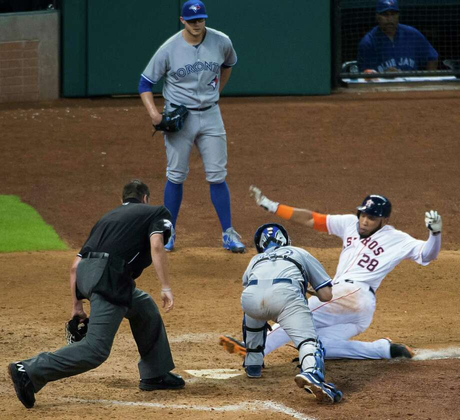 He originally was ruled out, but a review of the play showed that Astros first baseman Jon Singleton slid under the tag of Blue Jays catcher Josh Thole to complete an inside-the-park home run in the eighth inning. Photo: Smiley N. Pool / © 2014  Smiley N. Pool