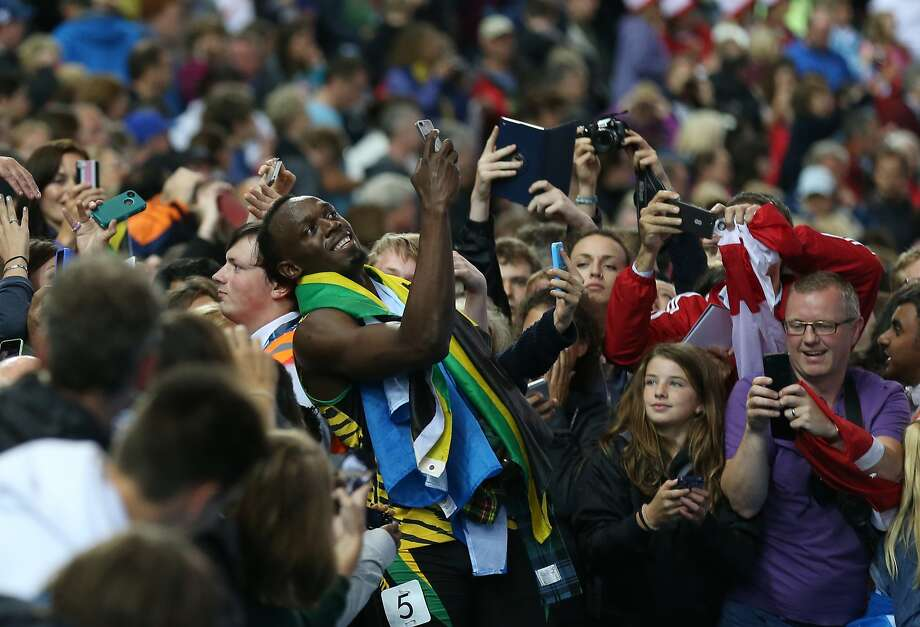 Usain Bolt of Jamaica takes a photo on a smart phone with a member of the crowd as he walks round Hampden Park Stadium after he competed in the men's 4x100 meter relay race during the Commonwealth Games 2014 in Glasgow, Scotland, Saturday Aug. 2, 2014. (AP Photo/ Scott Heppell) Photo: Scott Heppell, Associated Press
