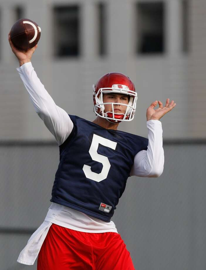 Quarterback John O'Korn throws a pass during opening football practice. Photo: Bob Levey